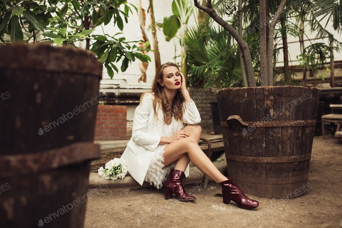 Young gorgeous woman in white jacket and dress thoughtfully look