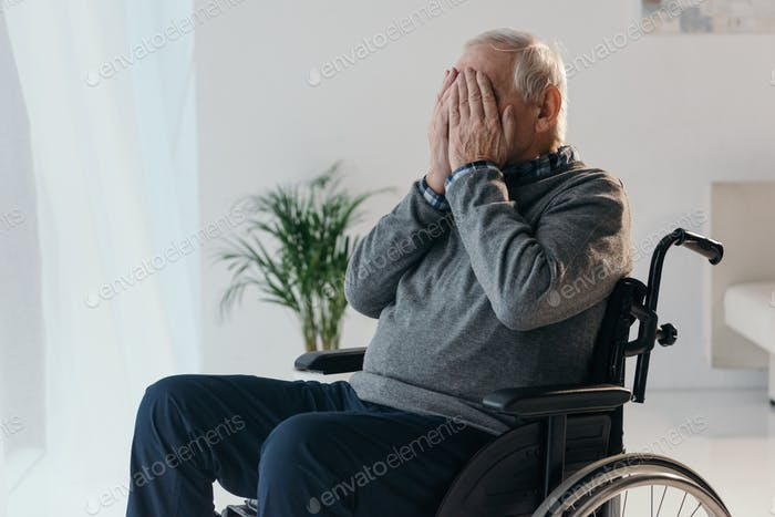 Senior sad man in wheelchair covering his face with hands
