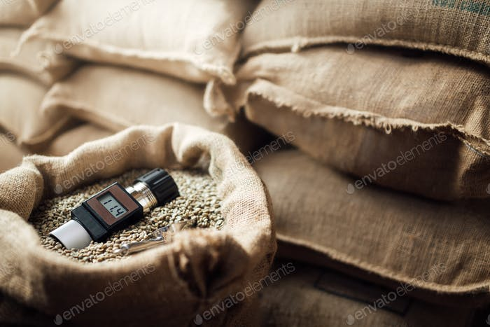working device for measuring the humidity of coffee beans in a bag , in the background
