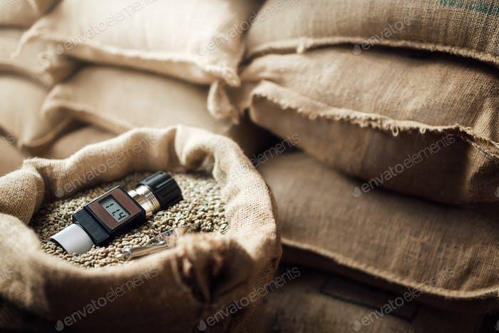Arbeitsgerät zur Messung der Feuchtigkeit von Kaffeebohnen in einer Tasche, im Hintergrund