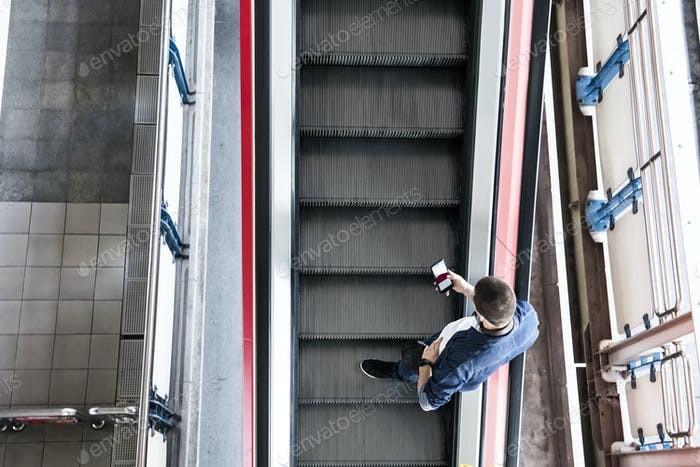 Man using a smartphone on the escalator