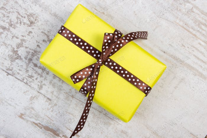 Yellow gift for Christmas, birthday or other celebration on wooden board
