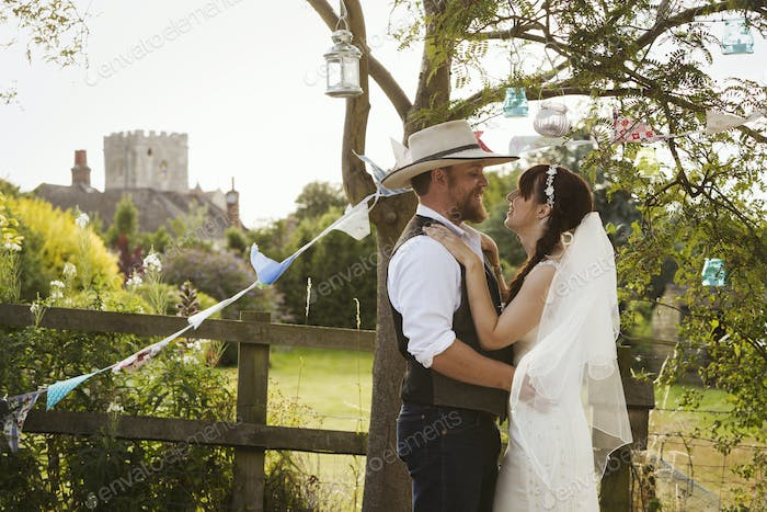 Newlywed couple, a bride and groom standing by a stile, hugging and gazing at each other.