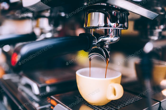 Close up details of brewing machinery pouring and preparing espresso. Cafe shop details