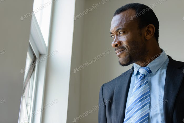 Handsome African bearded businessman looking out the window