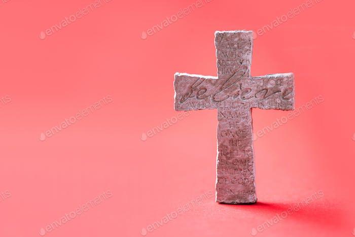 Steinkreuz mit Inschrift Believe auf rotem Hintergrund, Kopierraum. Christlicher Hintergrund. Biblisch