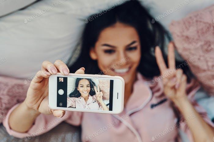 Draufsicht auf eine schöne junge Frau im Schlafanzug, die Selfie macht und lächelt, während sie zu Hause im Bett ruht