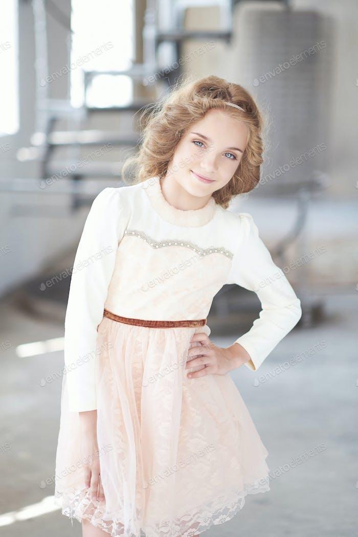 Glückliches kleines Mädchen Modell mit charmantem Lächeln posiert in einem Studio.