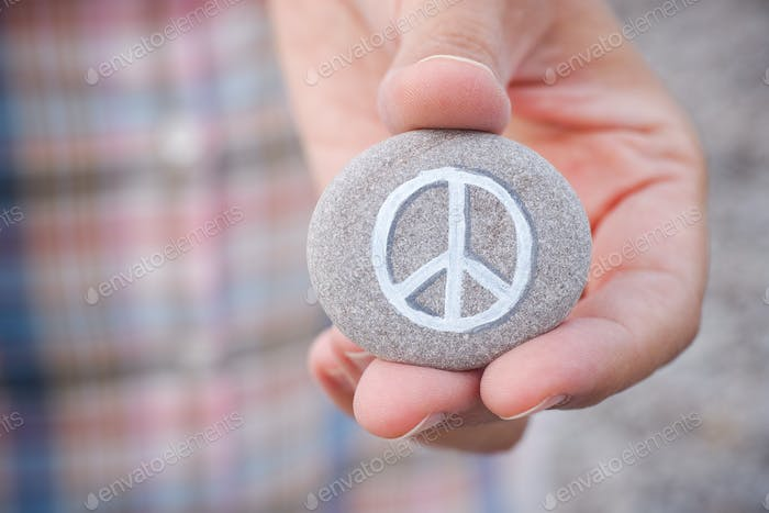 Person holds stone with peace symbol