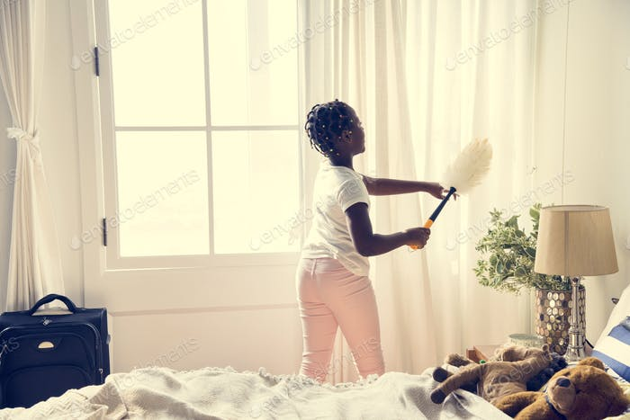 Young teen girl cleaning up the bedroom