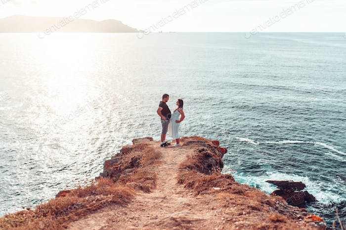 Pregnant couple joining their bellies on a cliff