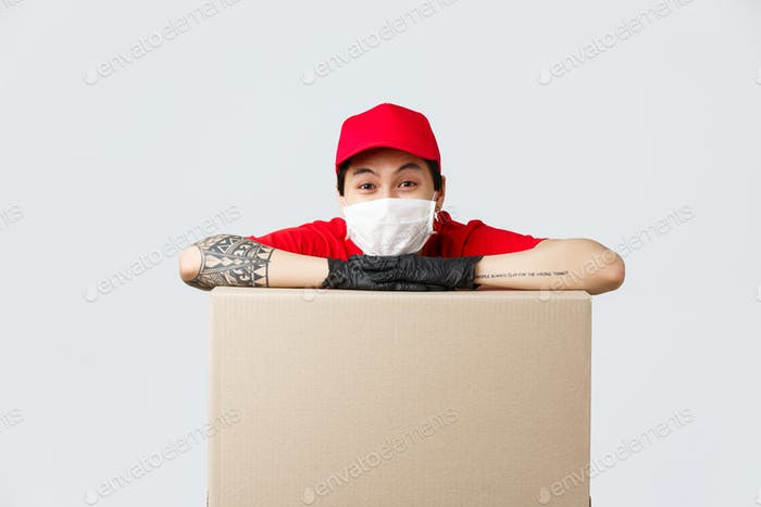 Delivery, online shopping and quarantine concept. Cheerful asian delivery guy in red cap uniform
