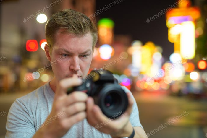 Face of young tourist man photographing with camera in the streets of Chinatown at night