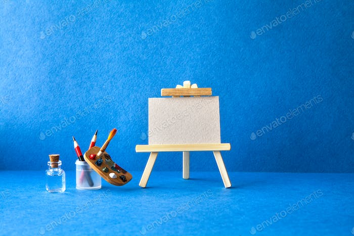 Wooden easel with textured blank paper canvas on blue background. Beautiful art class studio