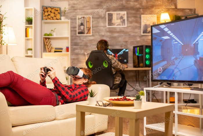 Woman lying on the sofa in living room playing video games using a virtual reality headset