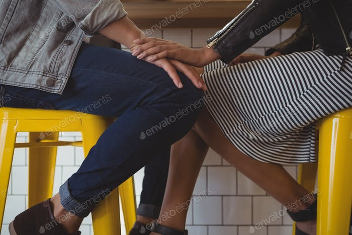 Low section of young couple on stool in cafe