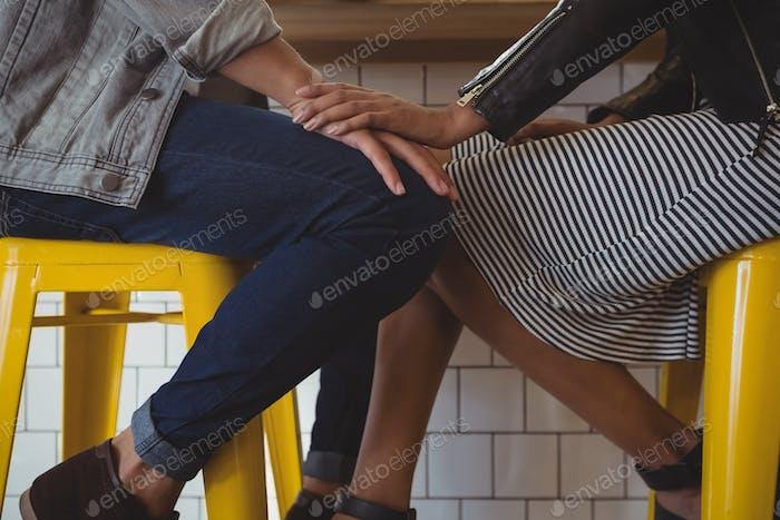 Niedriger Abschnitt des jungen Paares auf Hocker im Café