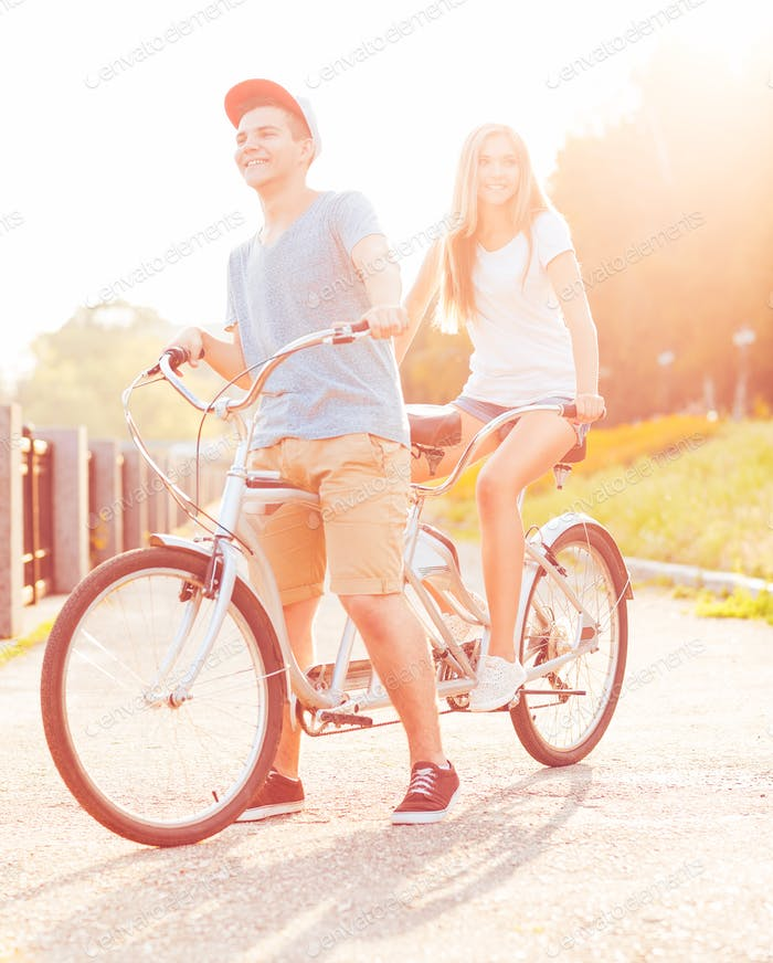 Thumbnail for Happy couple - man and woman riding a bicycle in the park outdoo