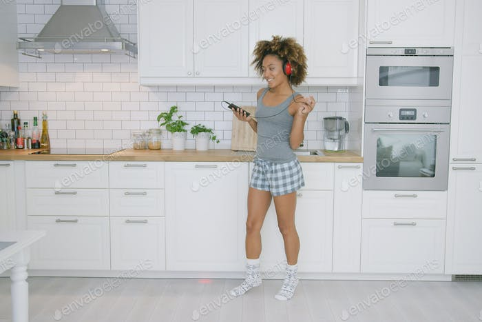Young woman dancing in kitchen with smartphone