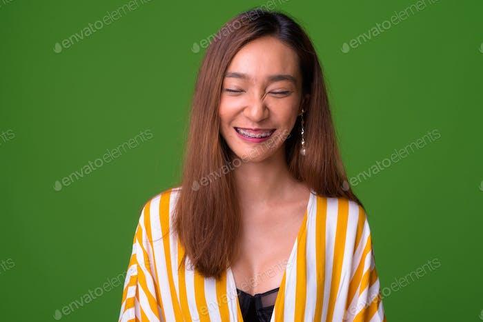 Junge schlanke asiatische Frau vor grünem Hintergrund