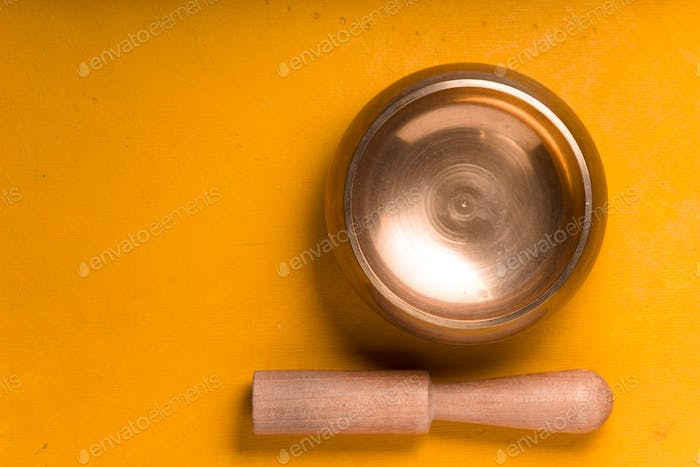 Metal bowl with wooden stick on the yellow table on the right