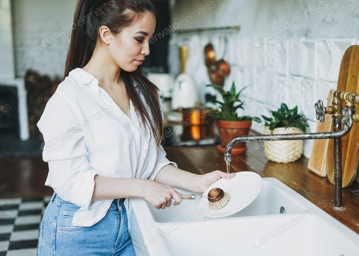 Young woman washes dishes with wooden brush with natural bristles at kitchen