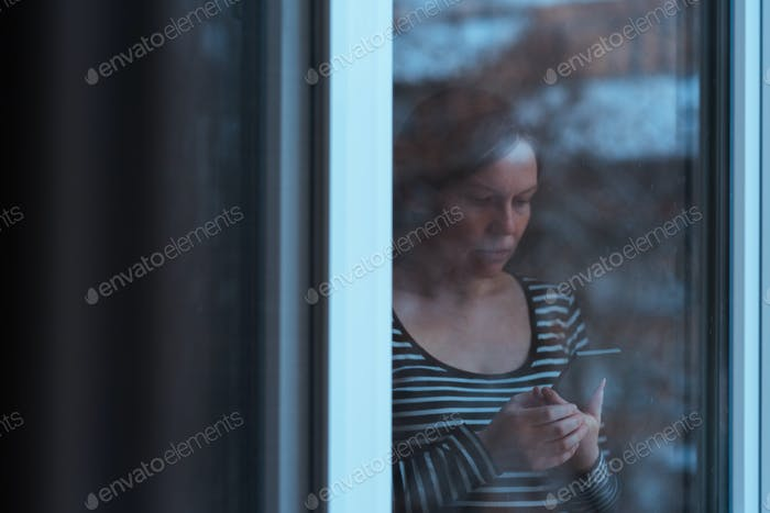 Alone sad man using mobile phone by the window