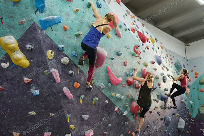 Three young sporty women in activewear grabbing by rocks on climbing equipment