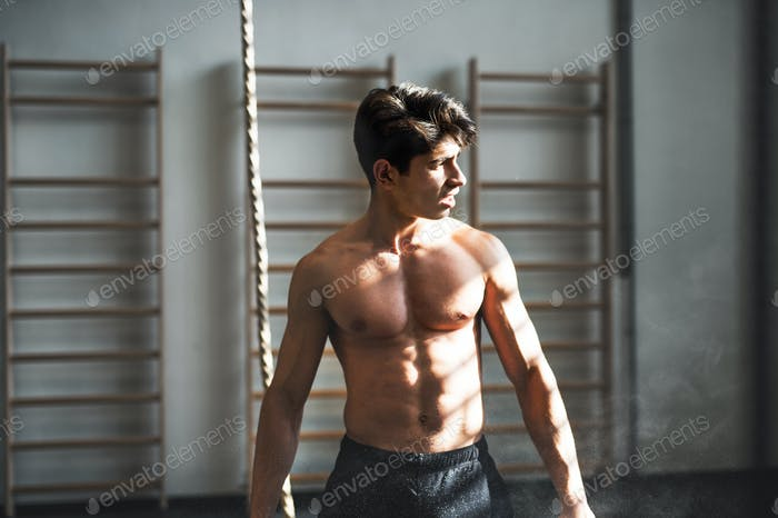 Fit young man in gym standing topless in front of a climbing rope.