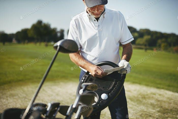 Senior Mann liest seine Scorecard während eines Golfspiels