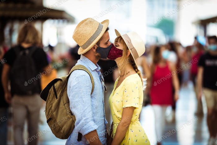 CCouple of lovers wearing protective face mask kissing each other in the city.