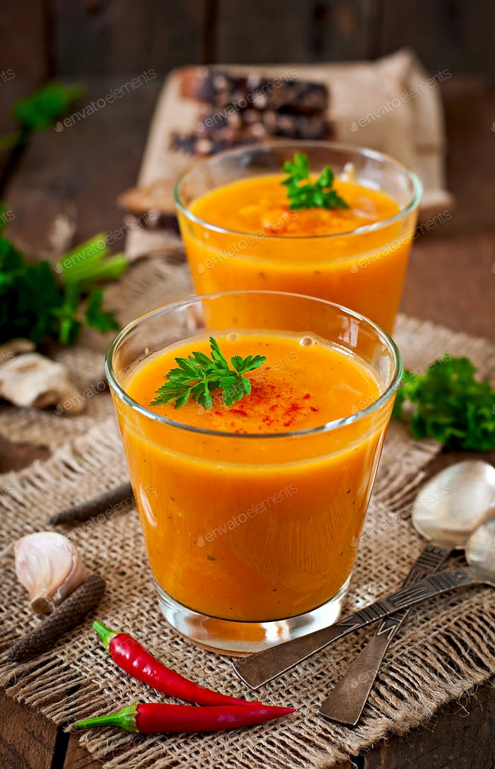 Delicious cream of pumpkin soup in a glass on wooden table