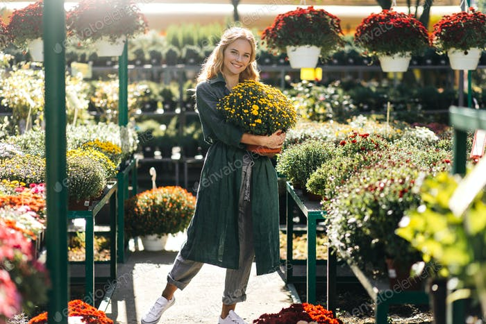 Horizontal photo of attractive woman with bright curls in shop with flowers and plants. Smiling mod