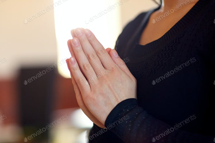 close up of sad woman praying god in church