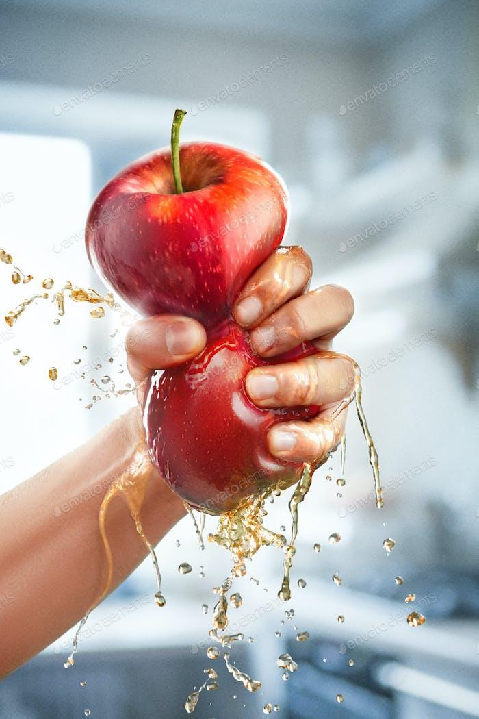 Eine männliche Hand drückt frischen Saft aus. Reiner Apfelsaft, der aus Früchten in Glas gegossen  wird