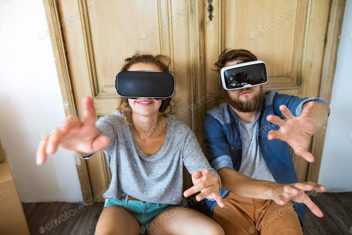 Young couple with VR glasses moving in new house.