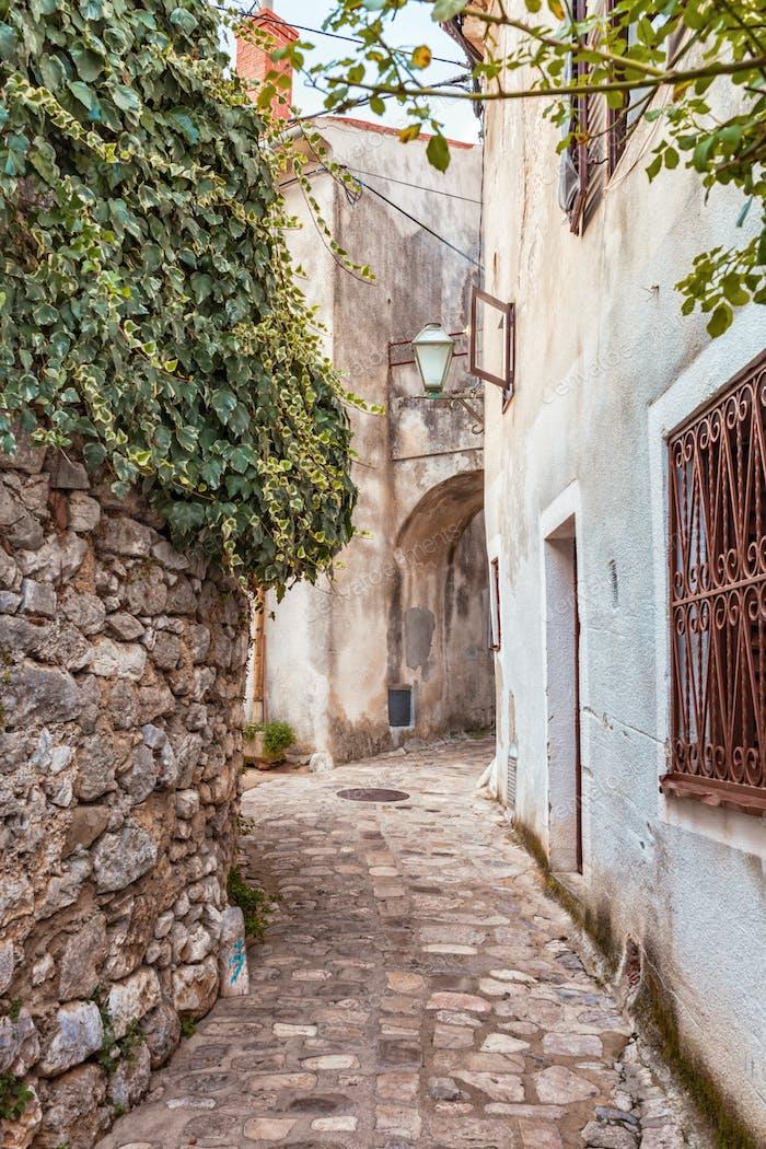 Narrow street with old stone houses in Krk Croatia