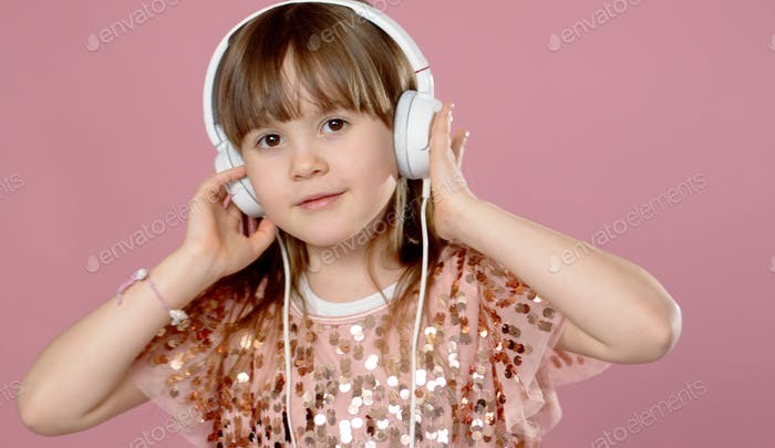 Cute little girl posing and dancing with headphones while listen to the music