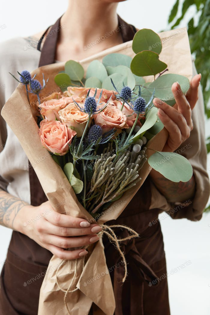 Fresh amazing flowers bouquet in a woman's hands with tattoo on a white background. Greeting