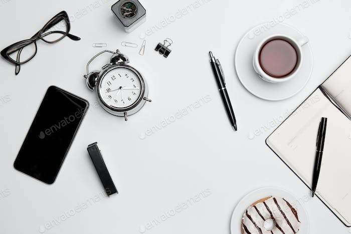 Office desk table with cup, supplies, phone on white background