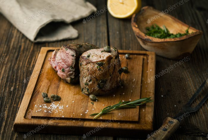 Roast beef steak with spices, seasonings and capers