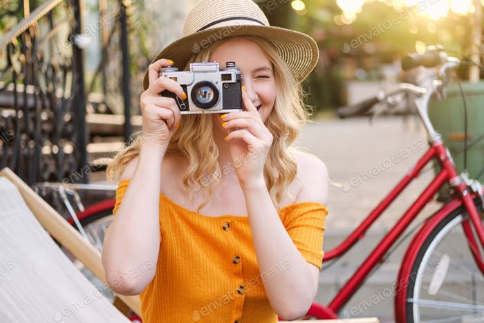 Smiling blond girl in hat happily taking photo on film camera on deck chair in street cafe