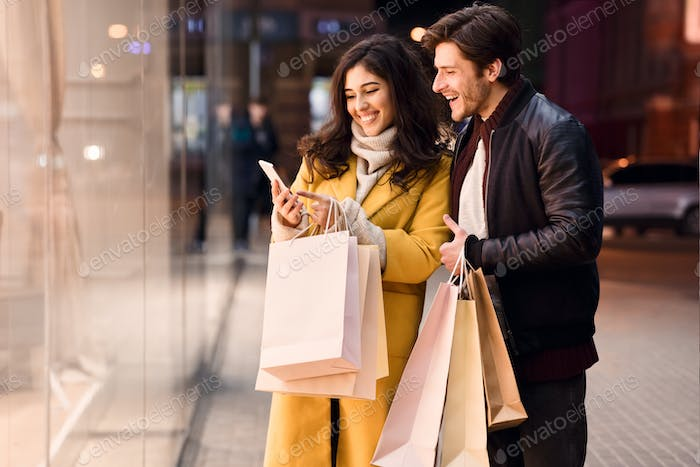 Young couple with smartphone near shopping mall