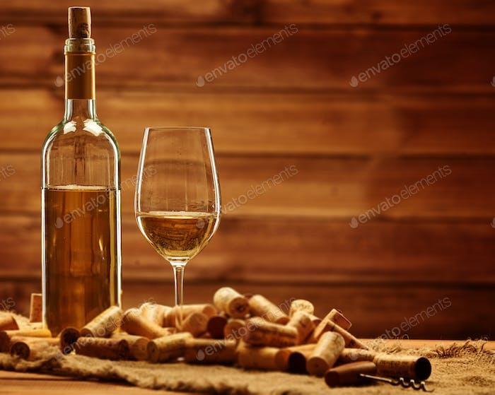 Botella y vaso de vino blanco sobre una mesa de De madera entre corchos