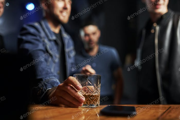 Focused photo. Friends in the bar. Man holds glass with whiskey