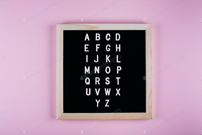 Back to school concept. Letters from A to Z on message board on pink background.