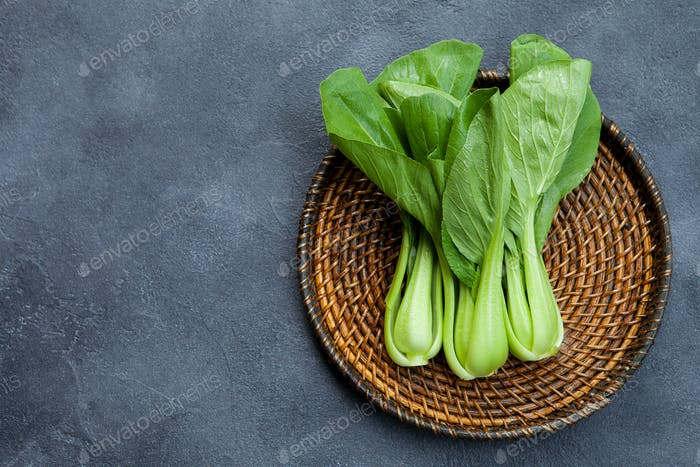 Bok Choy Fresh Salad on Wooden Plate. Grey Background. Top View. Copy Space.