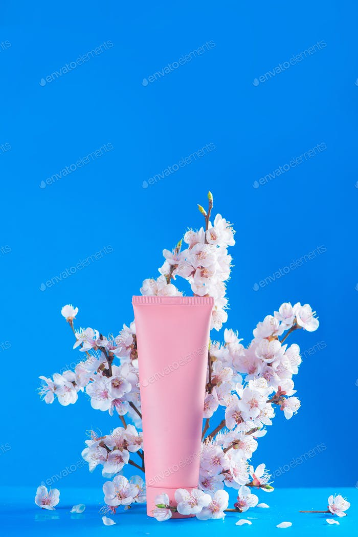 Cherry blossom cosmetics concept. Pink creme tube with spring flowers on a sky blue background with