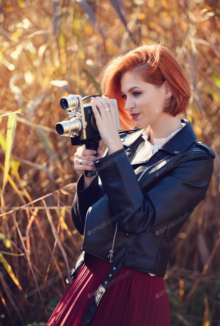 Beautiful young redhaired woman holds a video camera