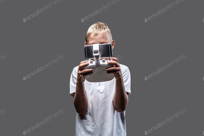 Blonde boy posing in a dark studio.